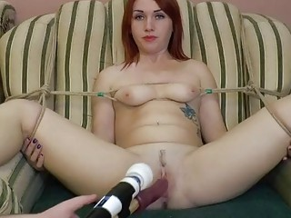 Tied up redhead reaches an orgasm while on camera