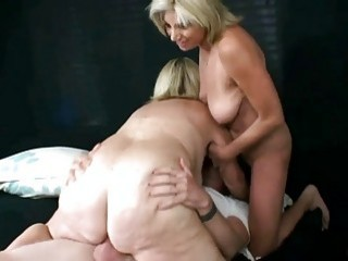 Two matures take care of a hard cock together