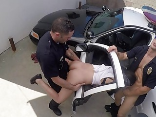 Two cops fuck a hooker on a police car outdoor